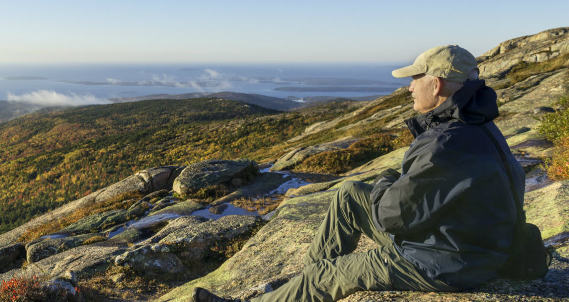 a man sitting on rocks looking out at a valley