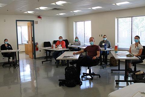 a group of nurses in a socially distanced classroom